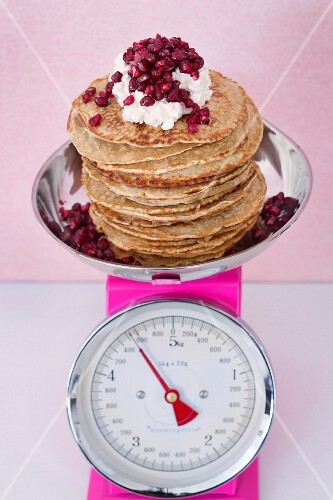 Wholemeal pancakes with cardamom, cream and pomegranate seeds
