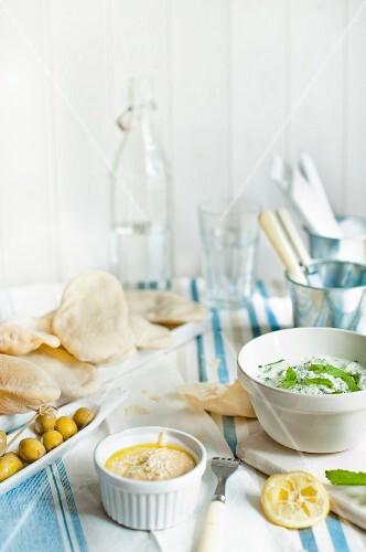 Tzatziki, hummus, unleavened bread and fresh olives
