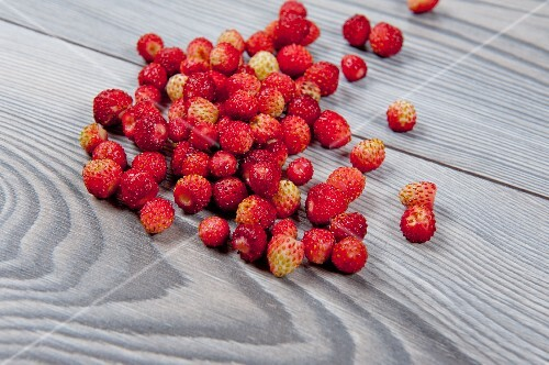 Fresh wild strawberries on a wooden surface
