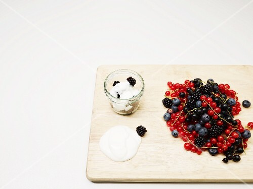 Fresh berries on a wooden board and yogurt with blackberries