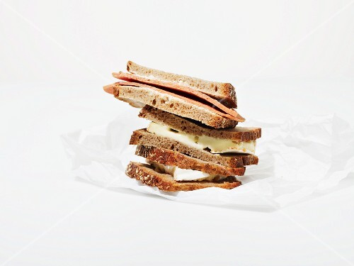 A stack of various sandwiches on a piece of greaseproof paper
