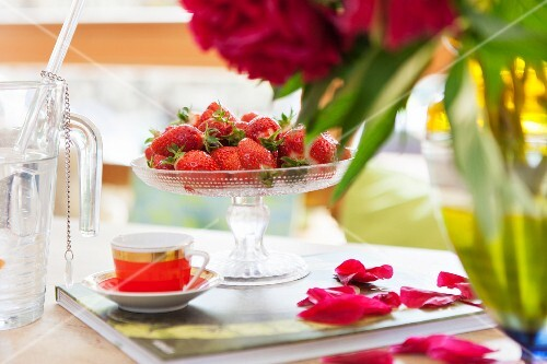 Fresh strawberries in a glass dish and a mocha cup on a book next to scattered rose petals