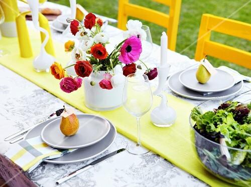 Colourful vase of ranunculus on festively set garden table
