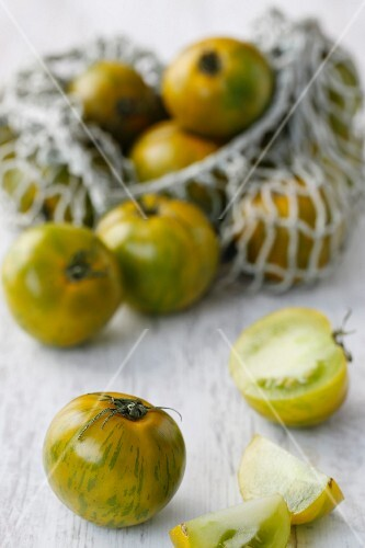 Green tomatoes, some in a net shopping bag