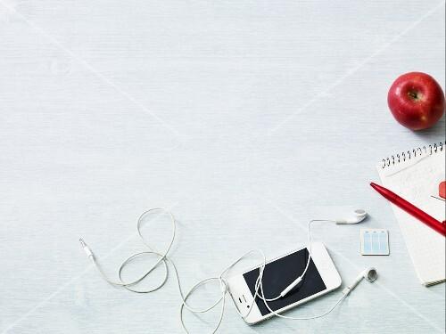 An arrangement featuring an apple, a shopping list and an iPod