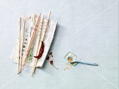 An arrangement of chopsticks on an oriental newspaper