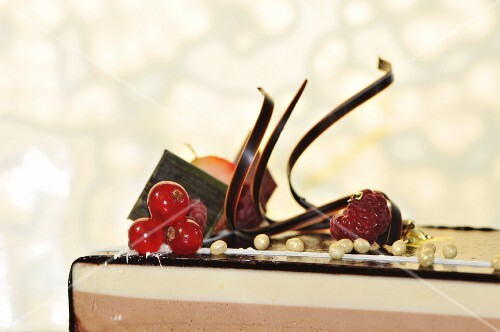 A three-layered chocolate cake topped with chocolate glaze and berries