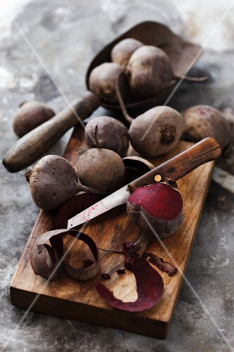 Cooked beetroots on a chopping board, one partially peeled