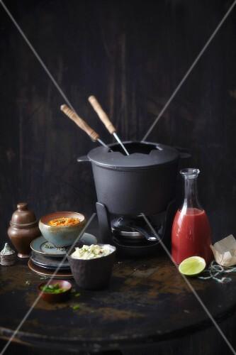 A fondue pot and fondue sauces