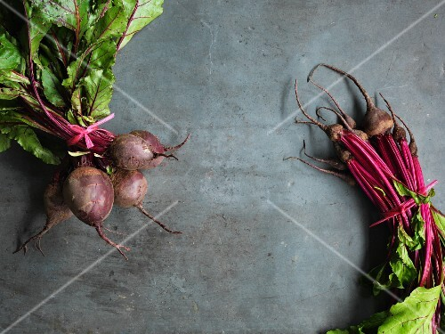 Two bunches of beetroot on a grey surface