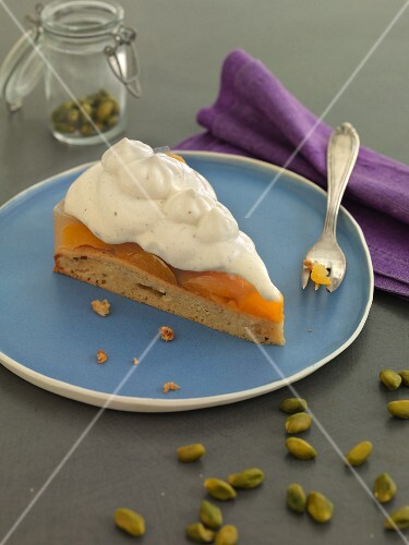 A slice of apricot cake with cream and pistachios