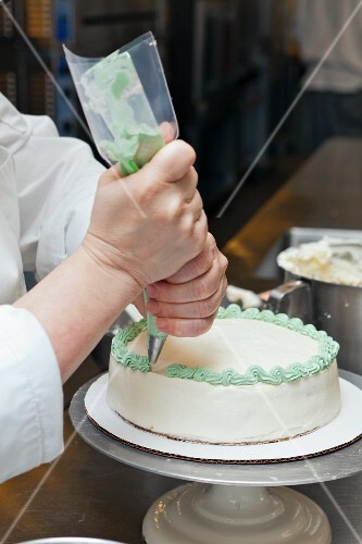 A chef icing a cake