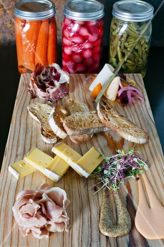 A platter of ham with pickles, crostini, mustard and Manchego cheese