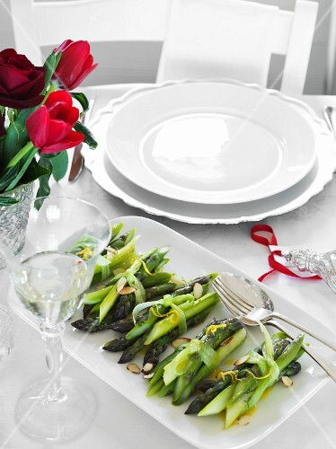 Cooked asparagus with lemon on a table set for Christmas dinner