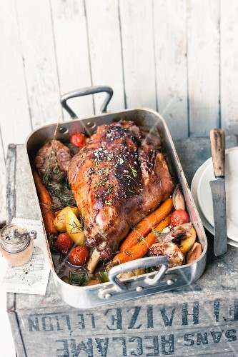 Leg of lamb in a roasting tin with vegetables