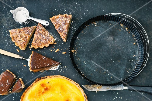 Slices of pine nut tart and chocolate tart with caramel and a whole orange tart
