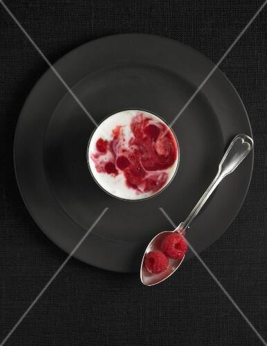 A raspberry yogurt drink with fresh raspberries