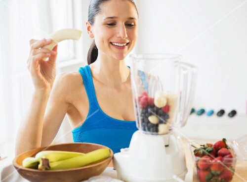A woman blending fruit to make a smoothie