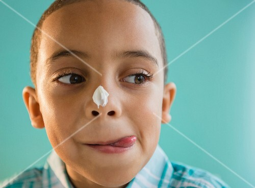 A boy with icing on his nose