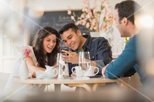 Friends looking at a mobile phone in a cafe