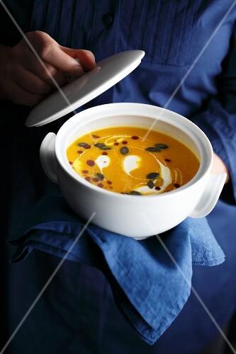 Cream of pumpkin soup with pumpkin oil and pumpkin seeds
