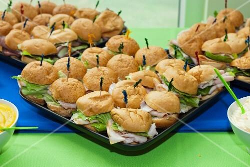 Viele Putensandwiches mit Eissalat auf Tablett
