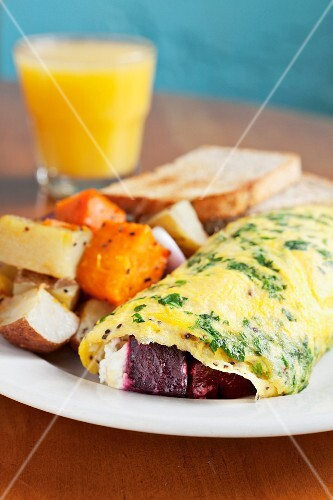 Omelette with beetroot, goat's cheese, parsley, roast potatoes, toast and orange juice