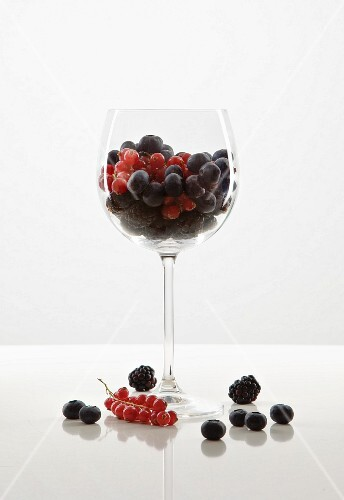 Berries in a wine glass against a white background