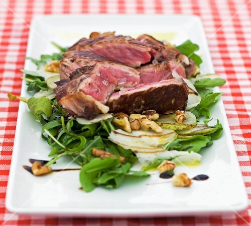 Grilled beef steak on a bed of lettuce