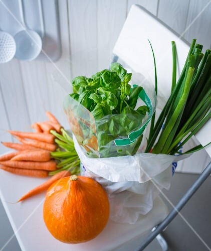 Fresh vegetables in a shopping bag on a kitchen chair