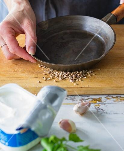 Korianderkörner mit Pfanne zerstossen