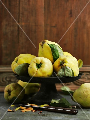 Quinces with leaves in a bowl in front of a wooden wall