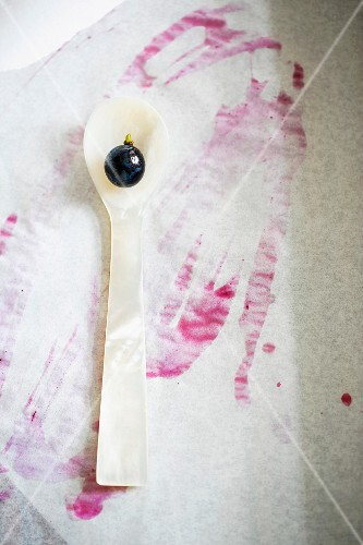 A red grape on a mother-of-pearl spoon with grape juice stains on a piece of paper