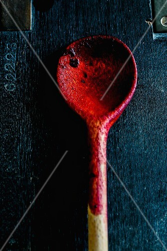The remains of grape jam on a wooden spoon on a wooden surface