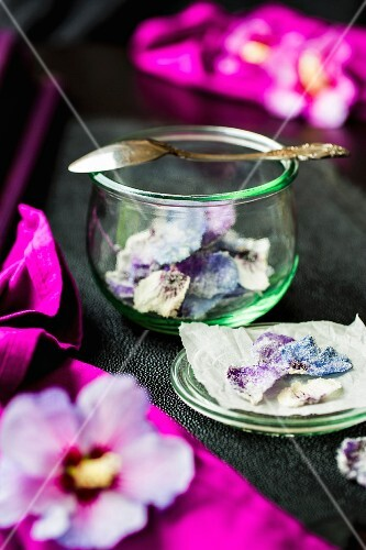 Candid hibiscus petals in a glass and on ray leather