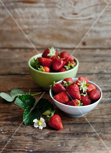 Bowls of fresh strawberries with leaves and flowers on a wooden surface
