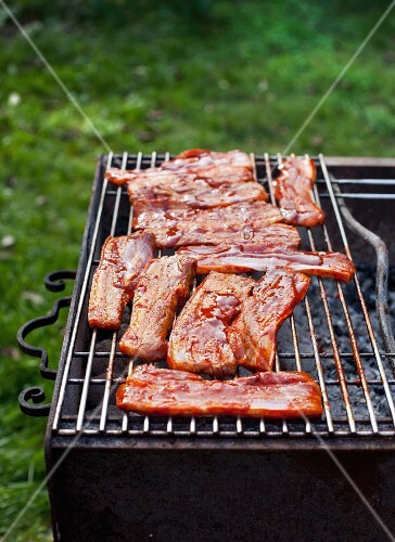 Marinated pork belly on a barbecue