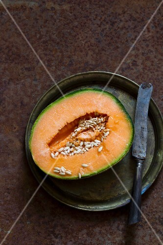 A halved cantaloupe melon on a pewter plate with an antique knife