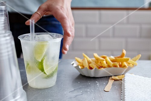 Chips in a paper dish with a drink in a plastic cup