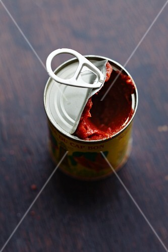 An opened tin of harissa (spicy chilli paste)