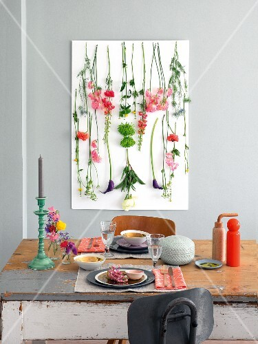 Flowers hanging from a picture hung on a pale grey wall with a table laid for two in front of it