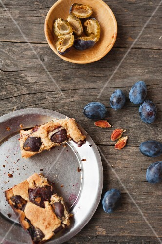 Plum cake on a metal plate and fresh plums on a wooden table