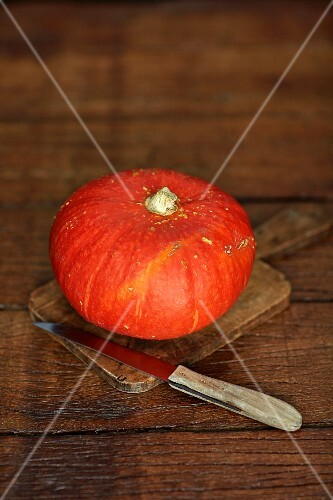 An orange pumpkin on a chopping board with a knife
