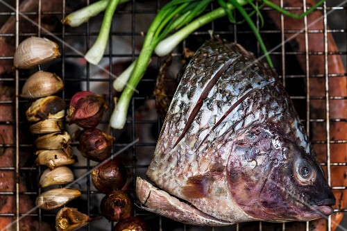A fish head, garlic and onions on a barbecue, Laos