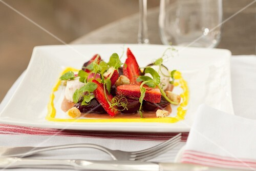 A small beetroot salad with chilli cream cheese, strawberries, pink pepper sauce and Parmesan croutons