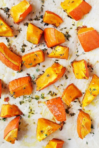 Diced pumpkin with thyme on a piece of baking paper