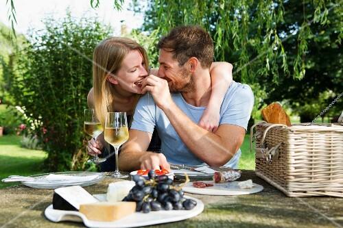 A man feeding his girlfriend at a picnic table in a garden
