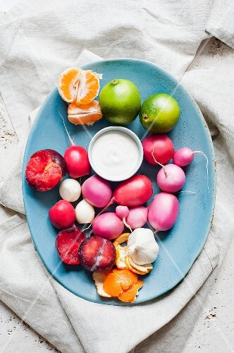 A plate of radishes, plums and citrus fruit with a dip