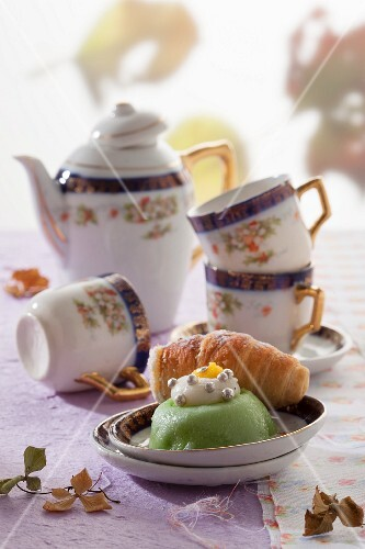 Cassata cake and a puff pastry roll filled with ricotta cream in front of an antique coffee service