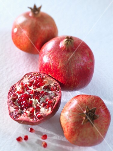 Three whole pomegranates and a halved one